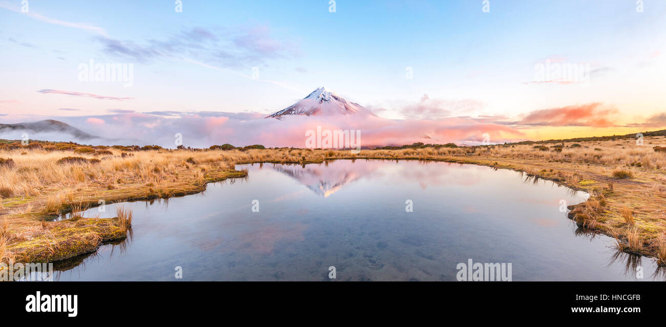 Reflection in Pouakai Tarn lake, pink clouds around stratovolcano Mount Taranaki or Mount Egmont at sunset, Egmont - Stock Image