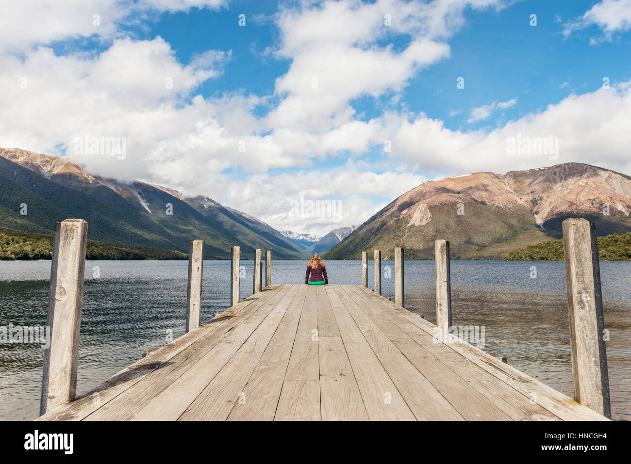 Woman sitting on dock, view of Lake Rotoiti, Nelson Lakes National Park, Tasman District, Southland, New Zealand - Stock Image