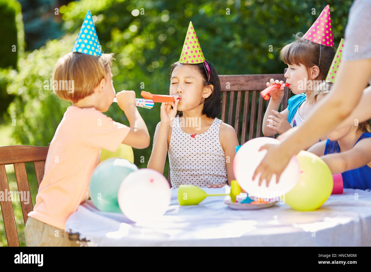 Kids having fun and celebrating with balloons at birthday party in garde - Stock Image