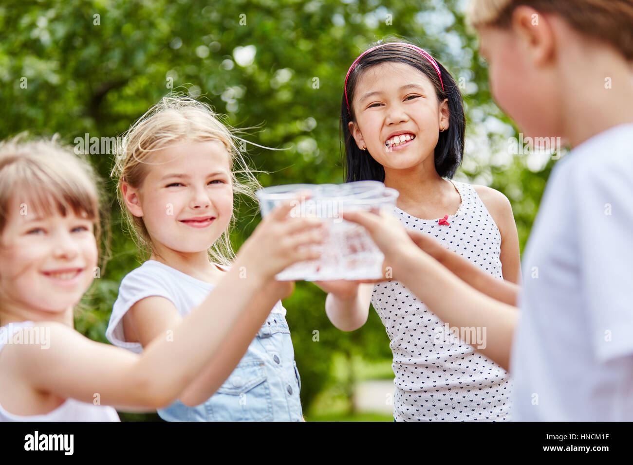 Three girls clinking their glasses of water at birthday party - Stock Image