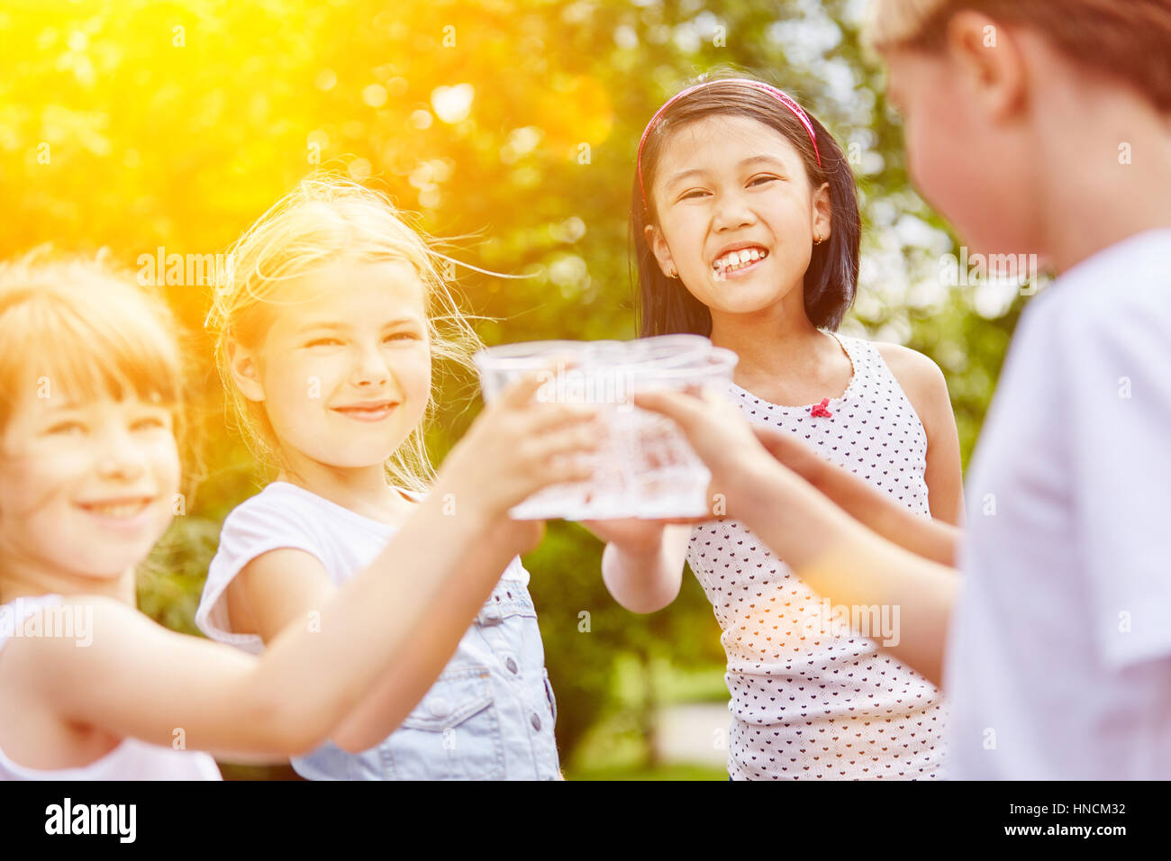 Group of girls drinking water in summer as friends at childrens birthday party - Stock Image