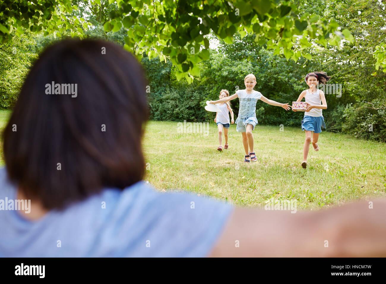 Children run to hug birthday child in her birthday party - Stock Image