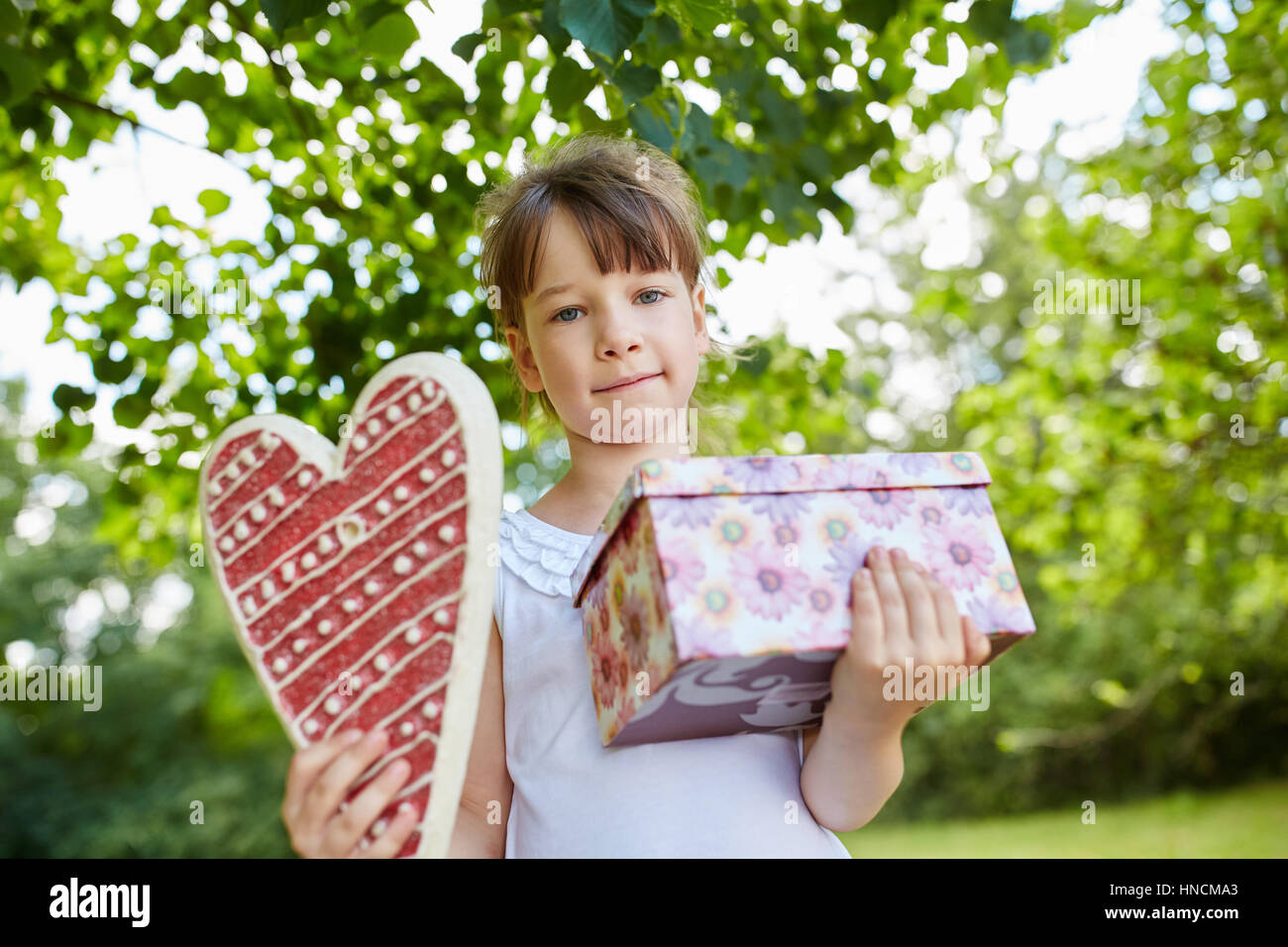 Child with birthday gift as a surprise at birthday party - Stock Image