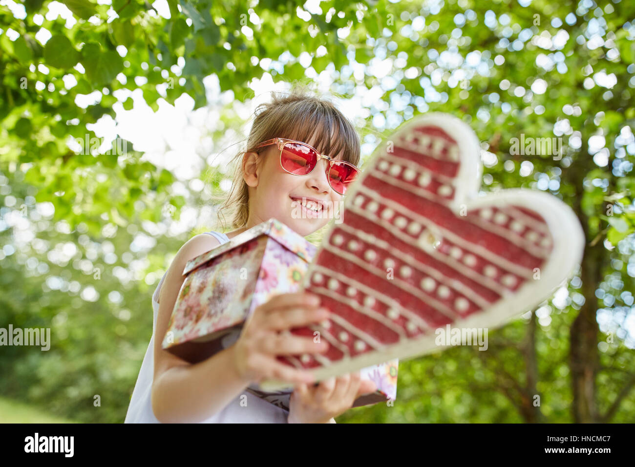 Girl at childrens birthday party in summer in the garden - Stock Image