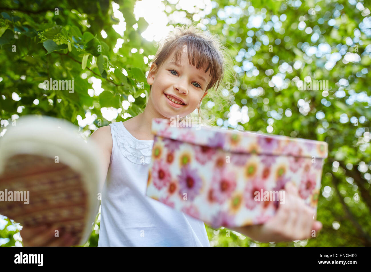 Girl with birthday gift at suprise birthday party smiles with joy - Stock Image