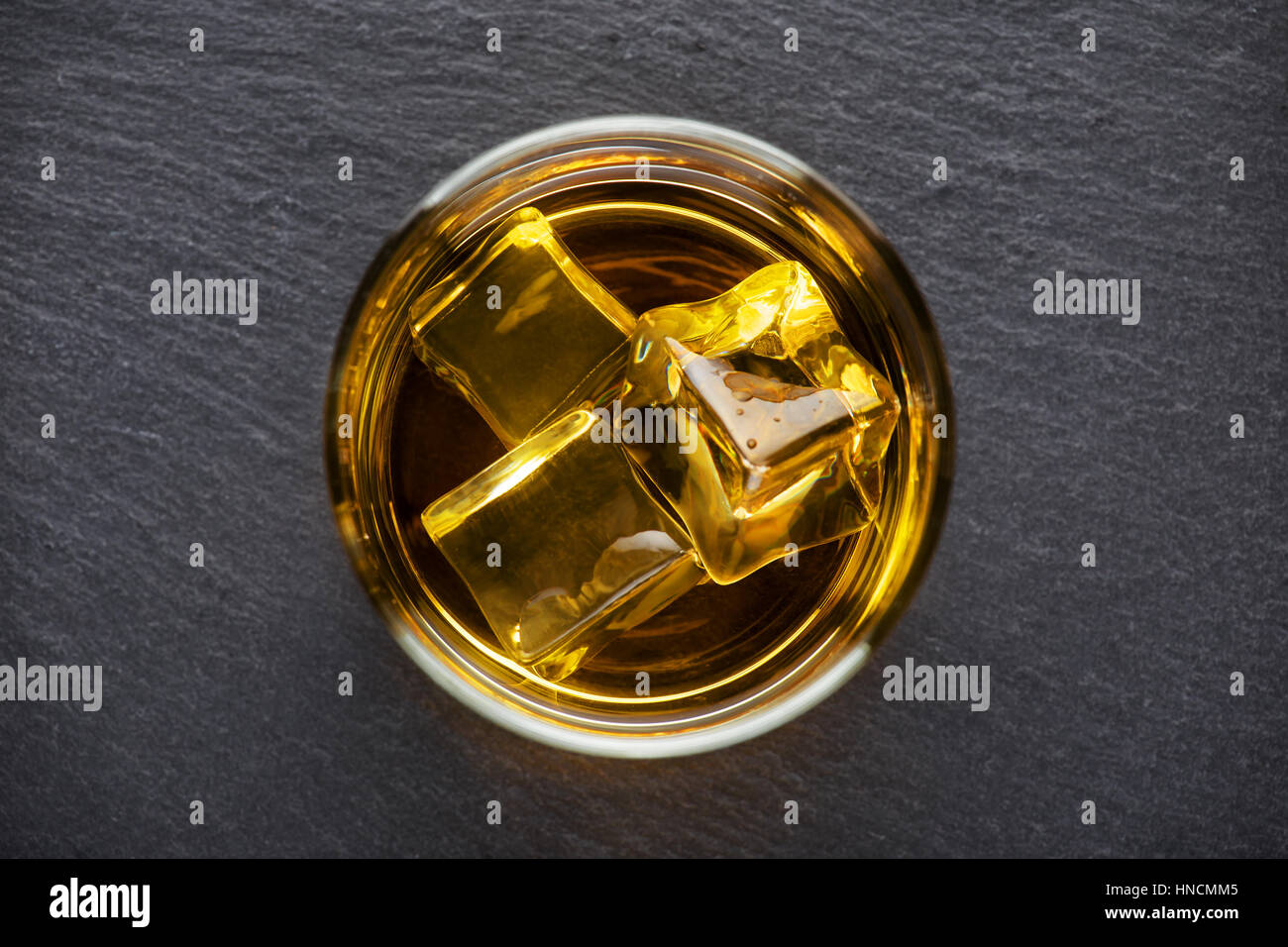 Round glass of whiskey with ice on a black background shot from above - Stock Image