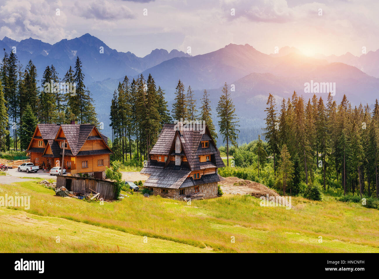 Traditional wooden house in the mountains on a green field Mount - Stock Image