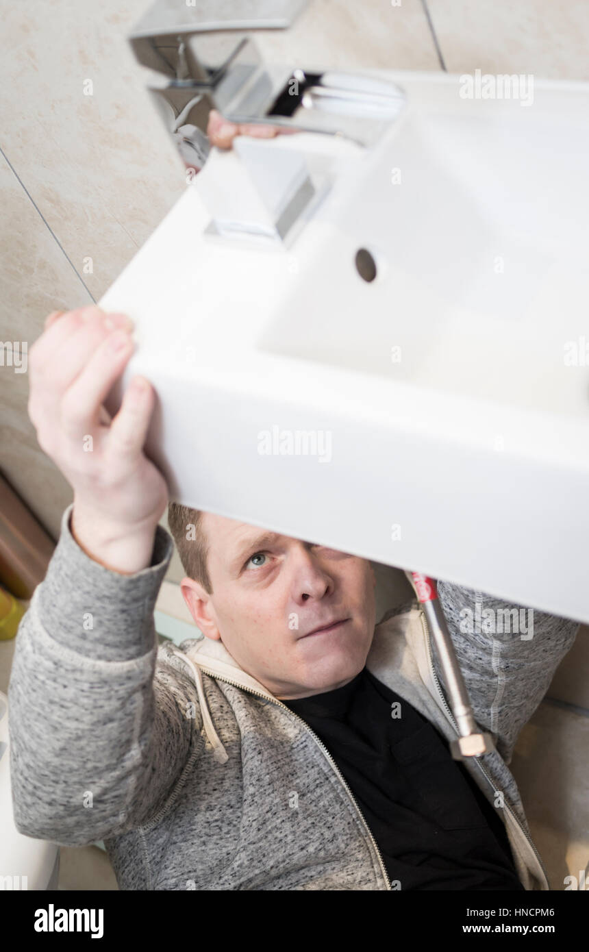 Young man attempting do it yourself diy plumbing at home under a young man attempting do it yourself diy plumbing at home under a sink fitting a new tap with a look of concentration on his face solutioingenieria Images