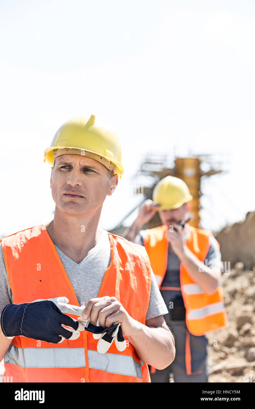 Thoughtful worker standing at construction site with colleague in background Stock Photo