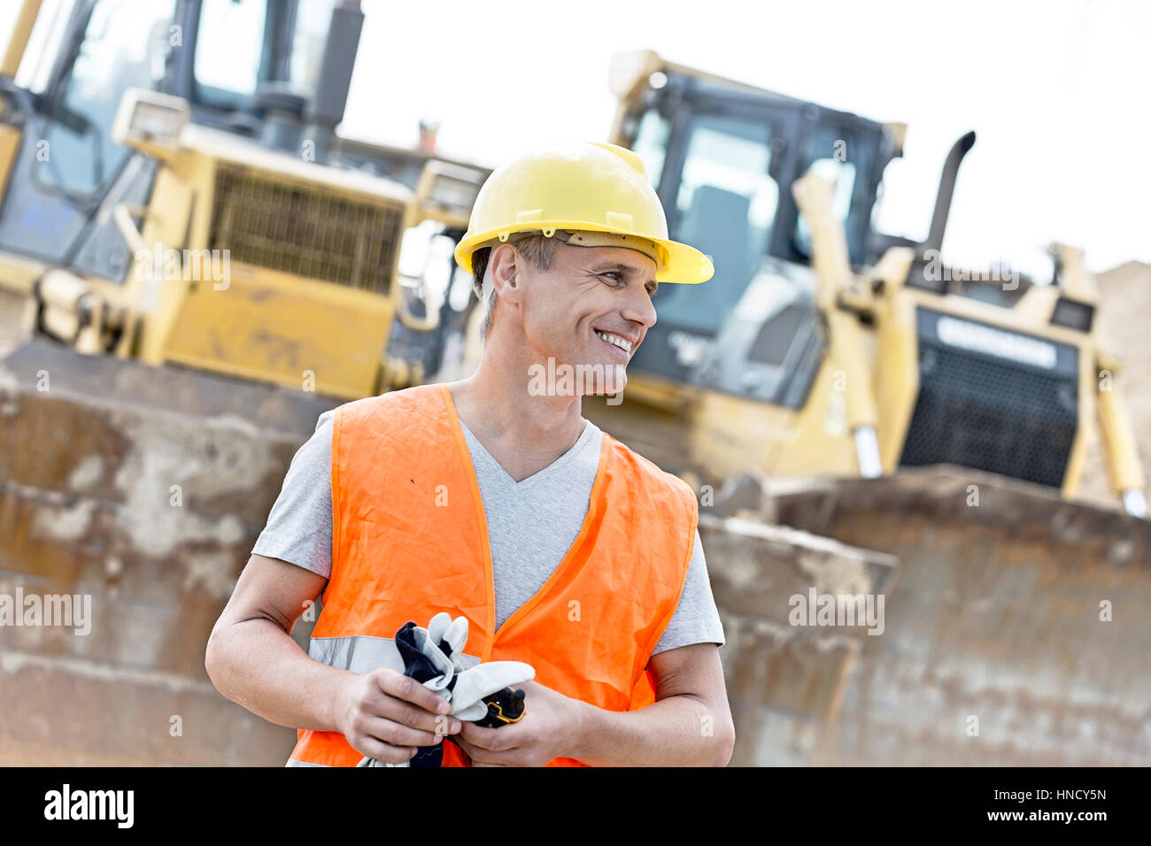 Happy supervisor looking away at construction site - Stock Image