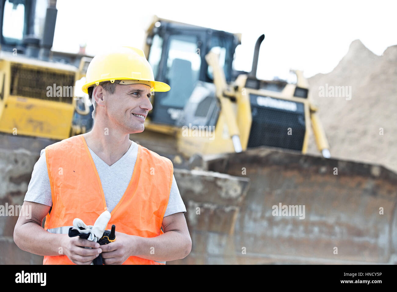 Smiling supervisor looking away at construction site - Stock Image