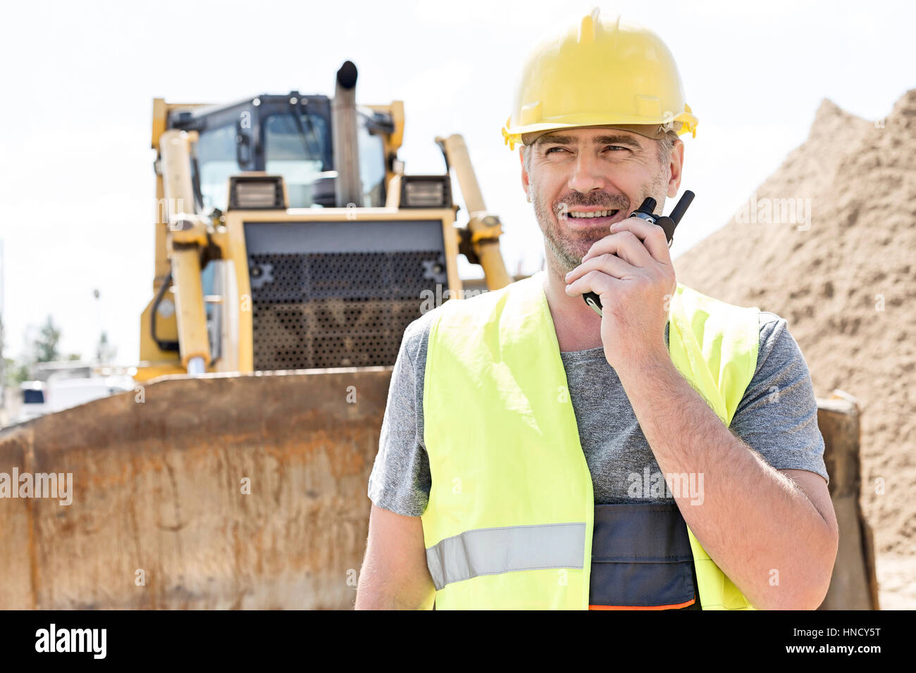 Confident supervisor using walkie-talkie at construction site - Stock Image