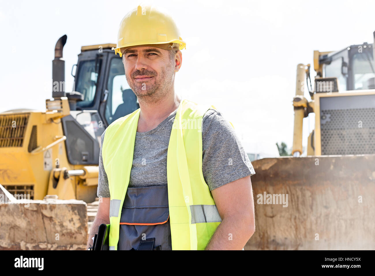 Portrait of confident supervisor standing at construction site - Stock Image