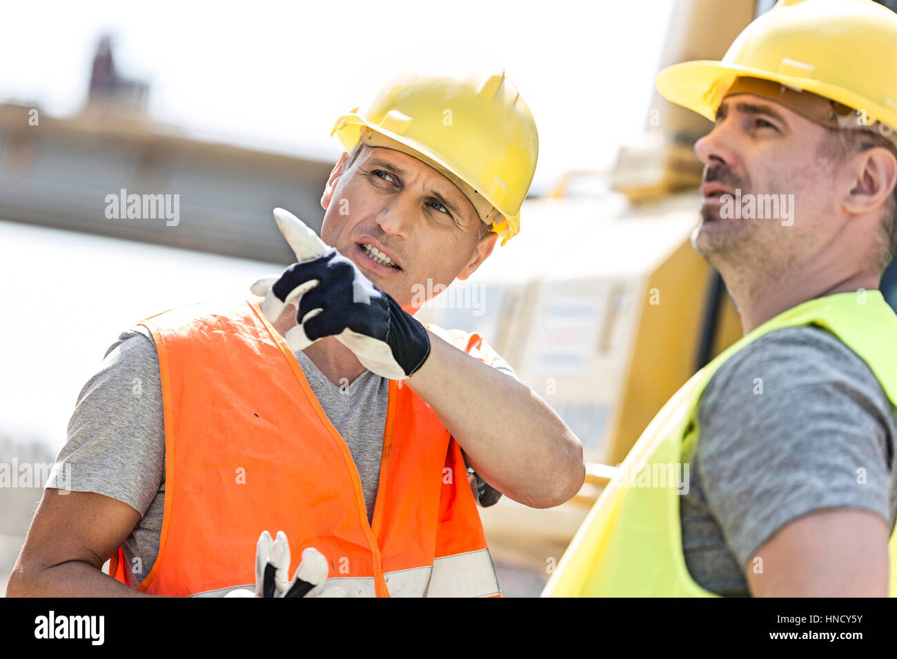 Supervisor showing something to colleague at construction site on sunny day - Stock Image