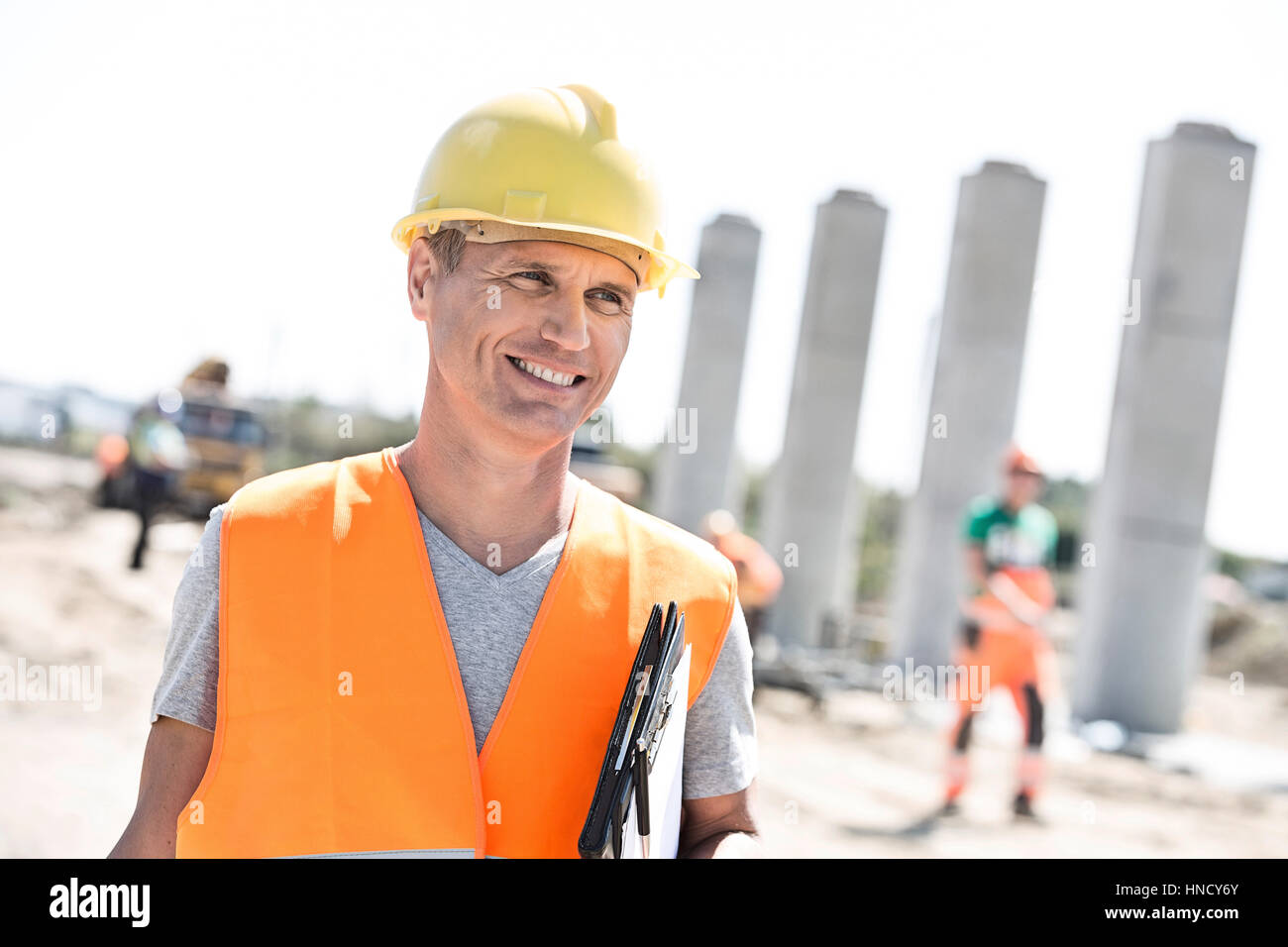 Happy architect looking away while holding clipboard at construction site - Stock Image