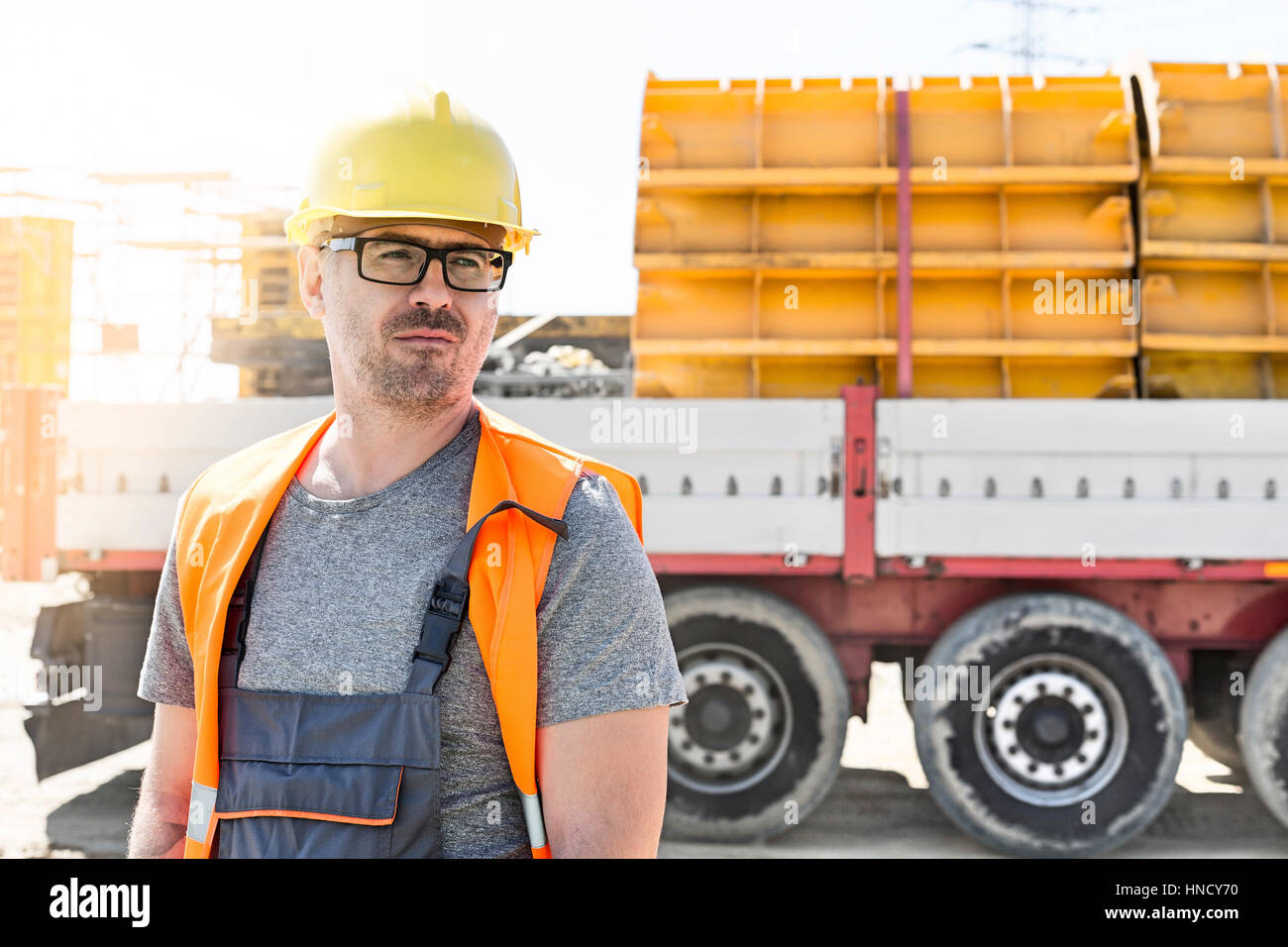 Thoughtful architect standing against truck at construction site - Stock Image