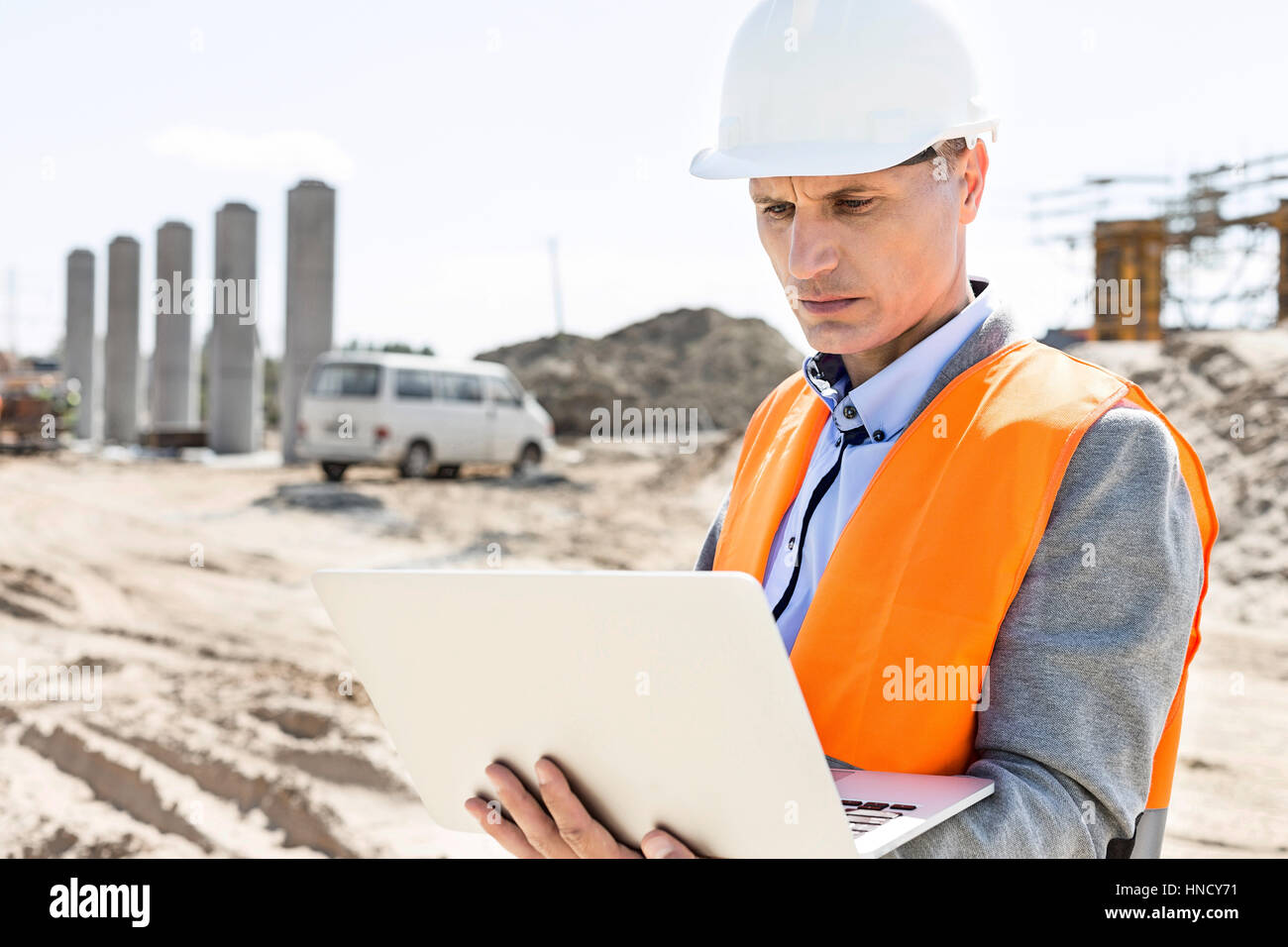 Supervisor using laptop at construction site on sunny day - Stock Image