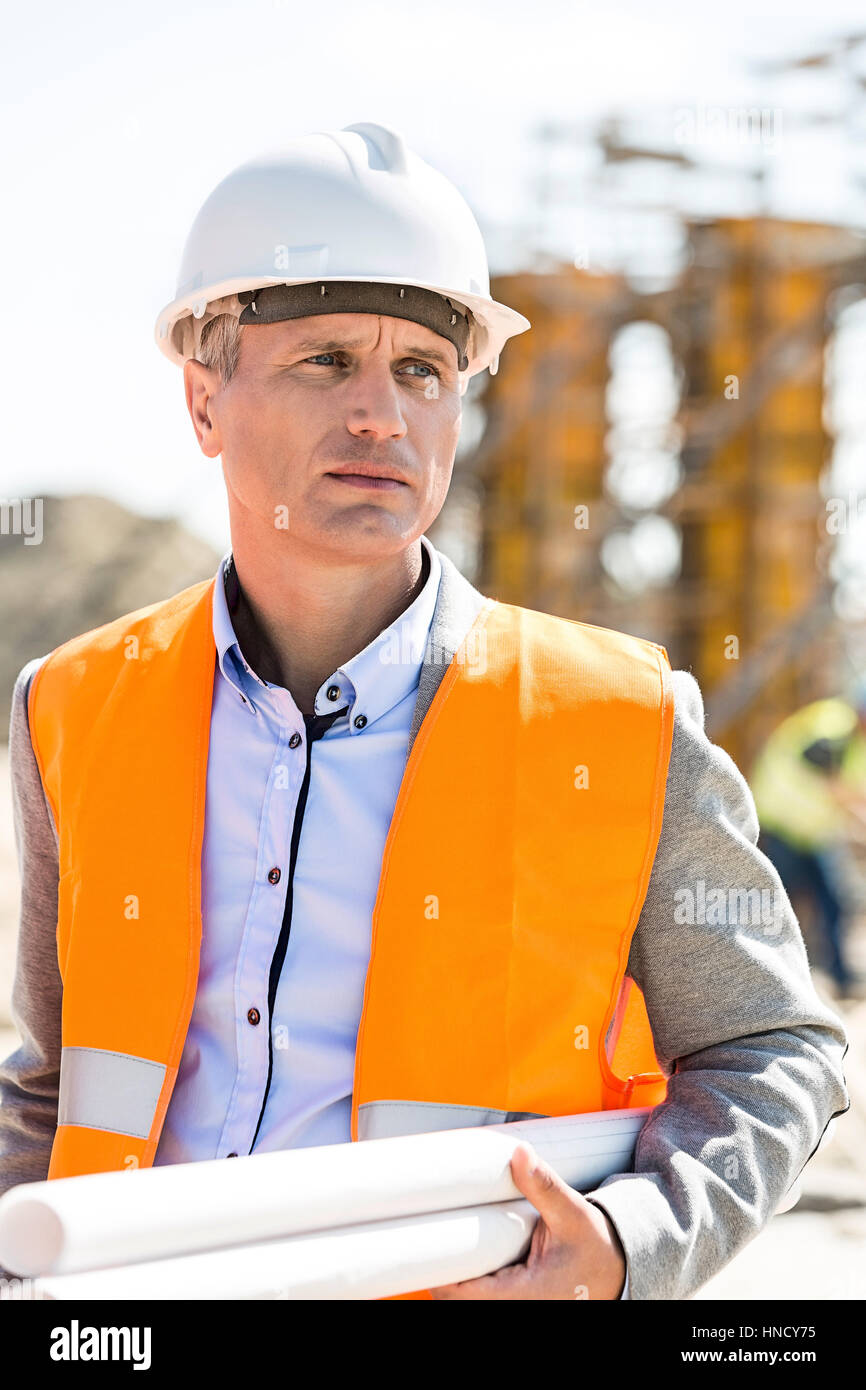 Thoughtful architect looking away while holding blueprints at construction site - Stock Image
