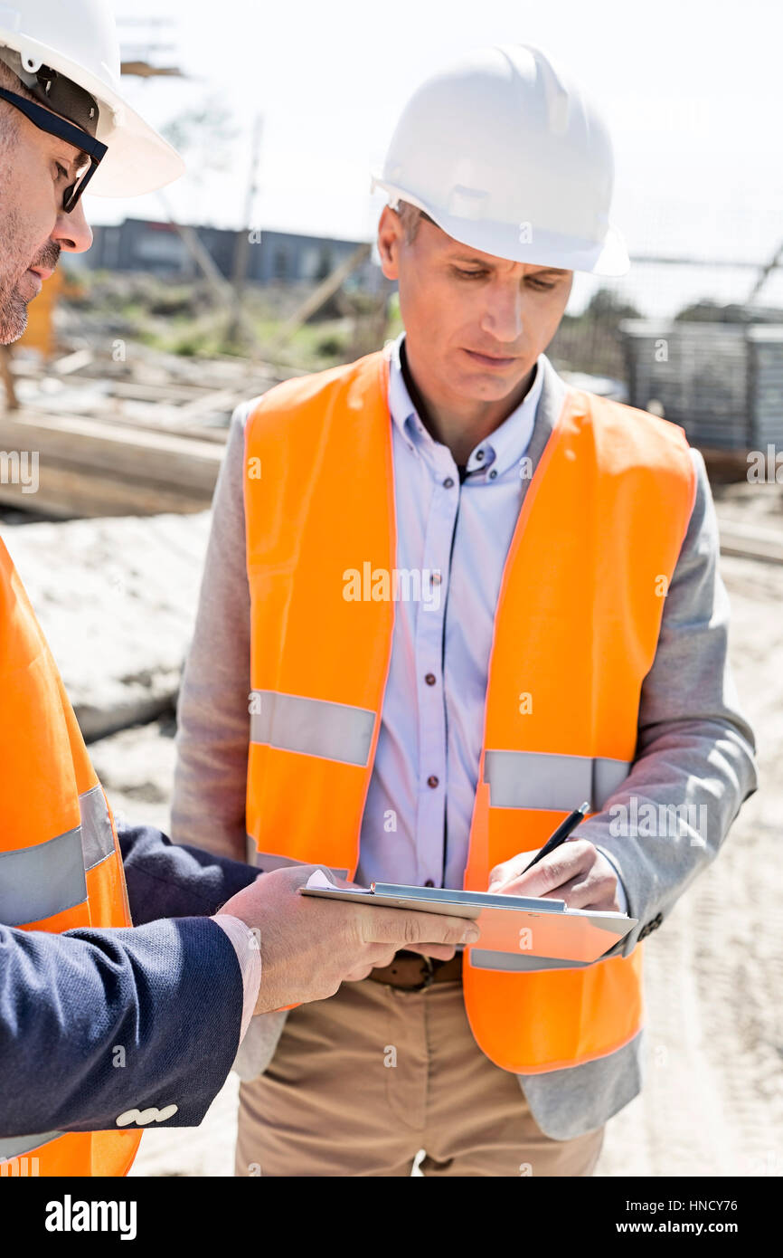 Engineers writing on clipboard at construction site - Stock Image