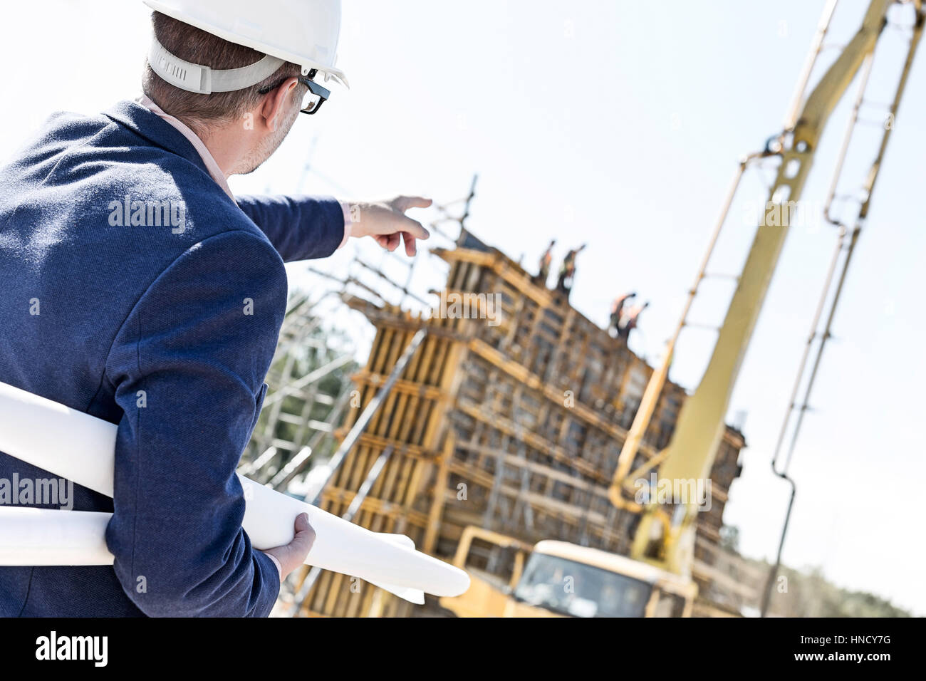 Tilt up construction stock photos tilt up construction stock rear view of architect holding blueprints while pointing at construction site stock image malvernweather Images