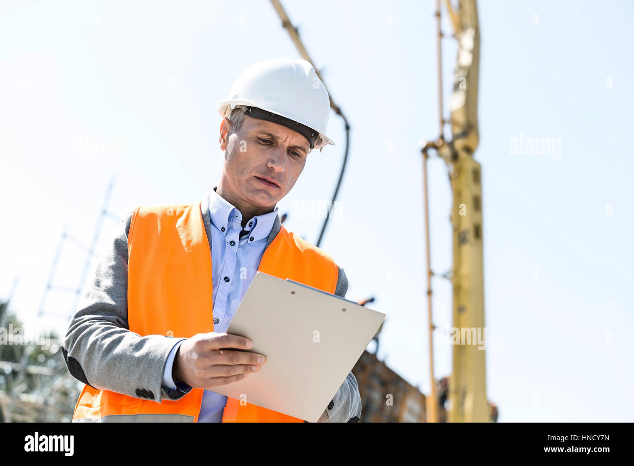 Low angle view of supervisor writing on clipboard at construction site - Stock Image