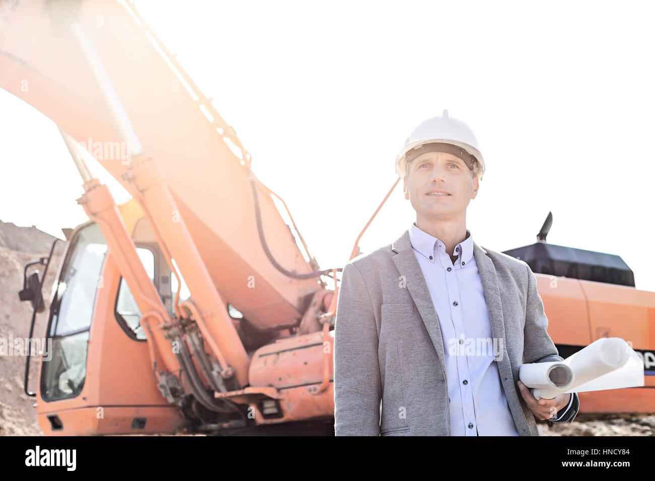 Thoughtful engineer looking away while holding blueprints by bulldozer at construction site - Stock Image