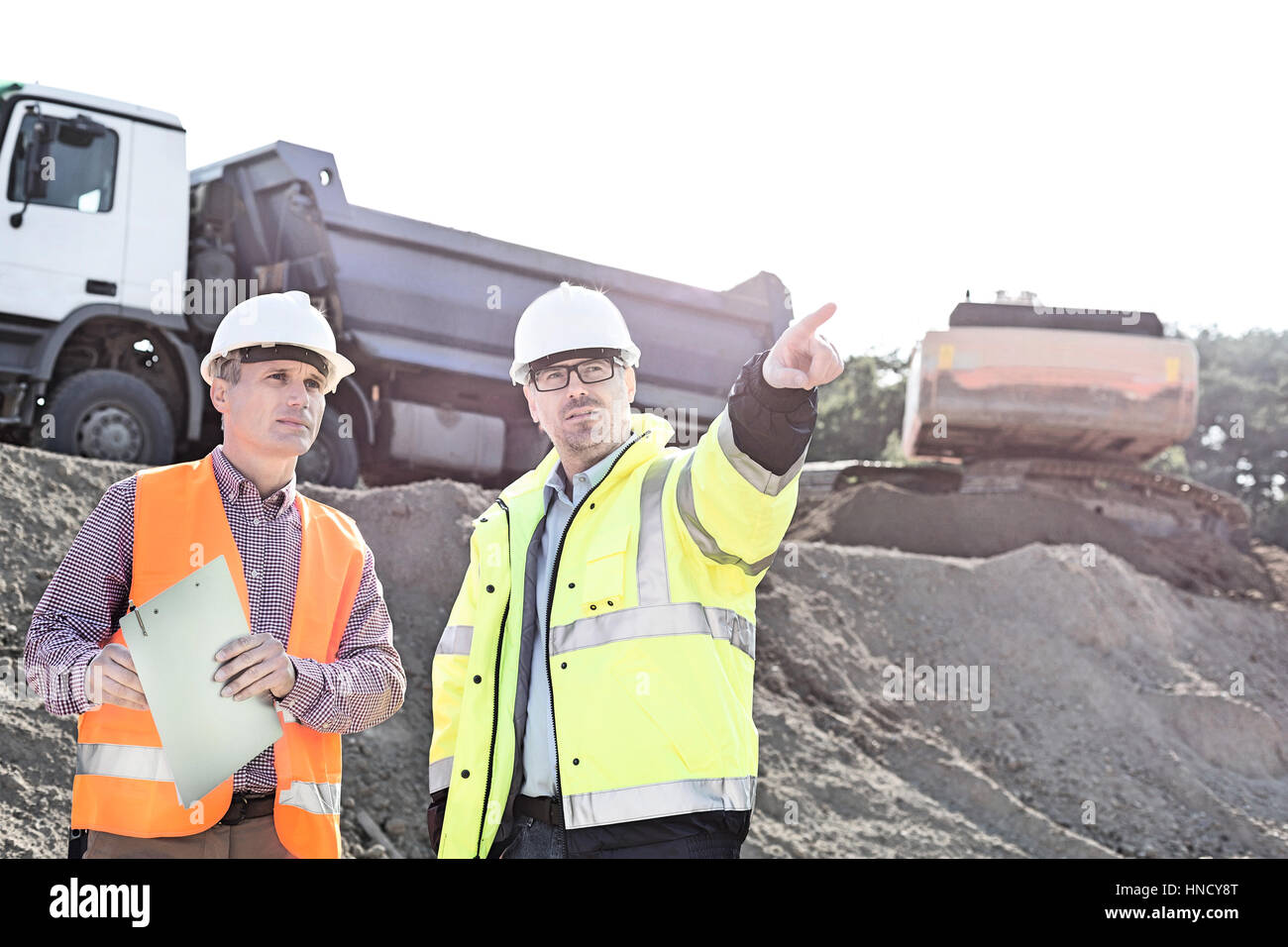 Supervisor showing something to colleague while discussing at construction site Stock Photo