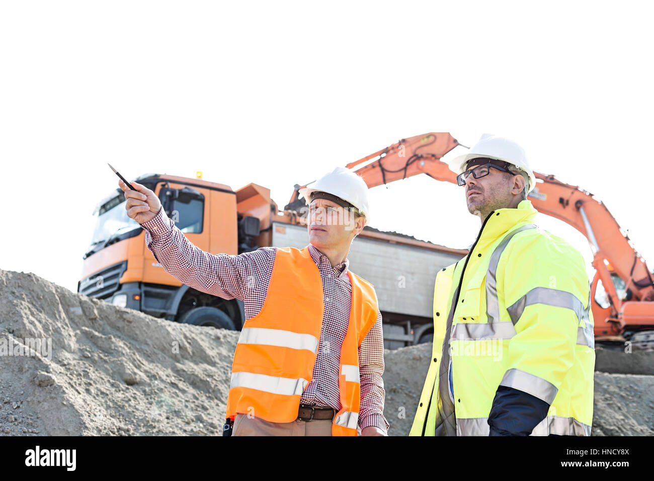 Engineer showing something to colleague while discussing at construction site against clear sky Stock Photo