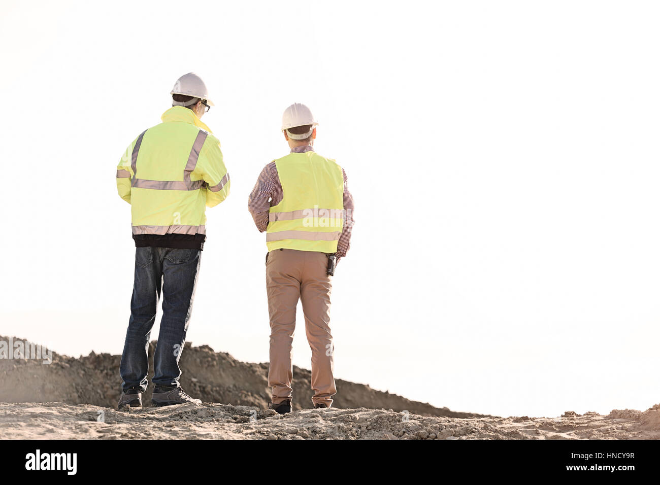 Rear view of architects standing at construction site against clear sky - Stock Image