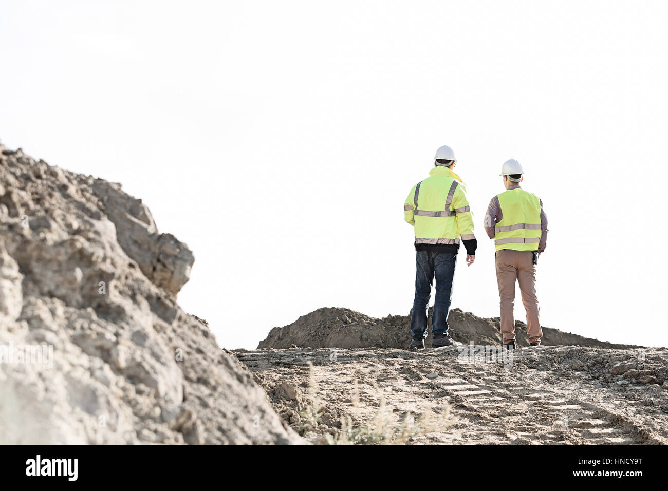 Rear view of supervisors standing at construction site against clear sky - Stock Image