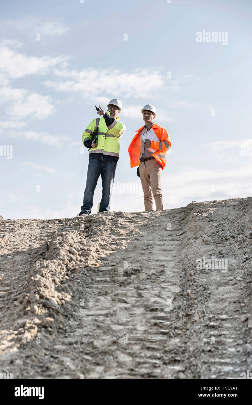Low angle view of architect showing something to colleague at construction site against sky Stock Photo
