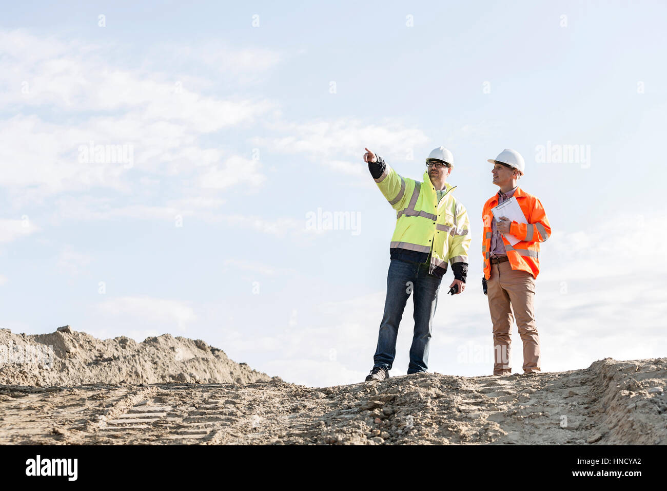 Low angle view of supervisor showing something to colleague at construction site - Stock Image