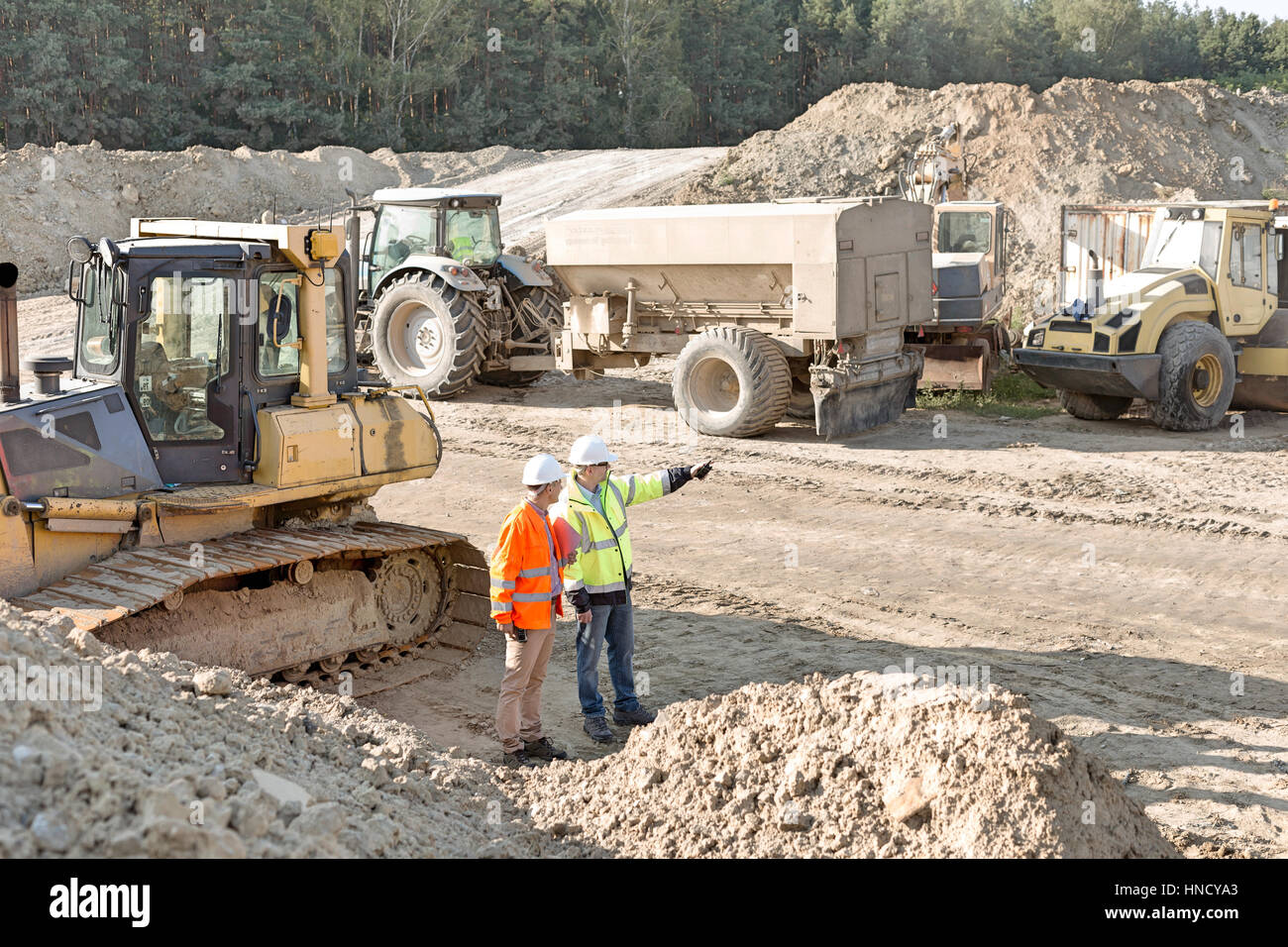 Supervisor showing something to colleague at construction site - Stock Image
