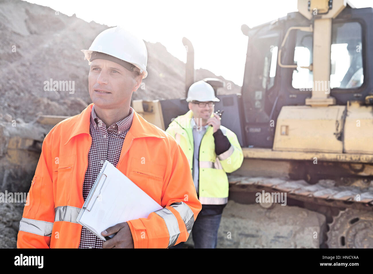 Engineer holding clipboard on construction site with colleague in background - Stock Image
