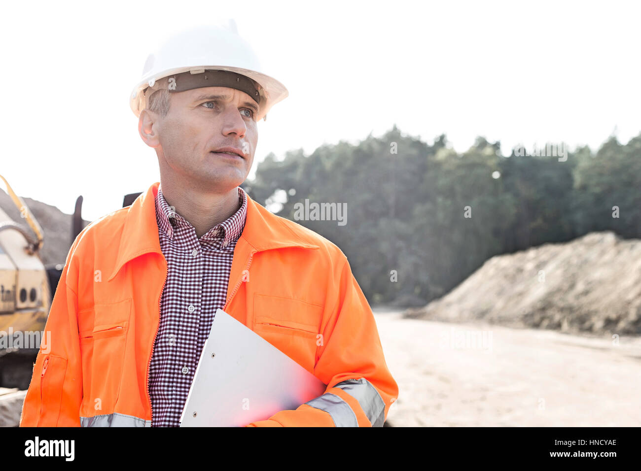 Thoughtful engineer holding clipboard against clear sky - Stock Image