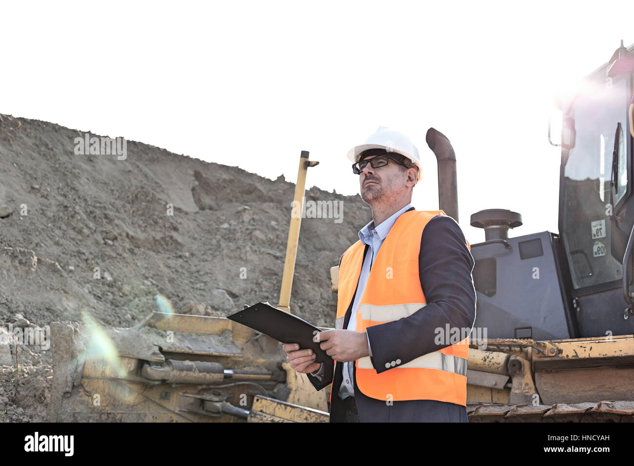 Engineer looking away while holding clipboard at construction site - Stock Image
