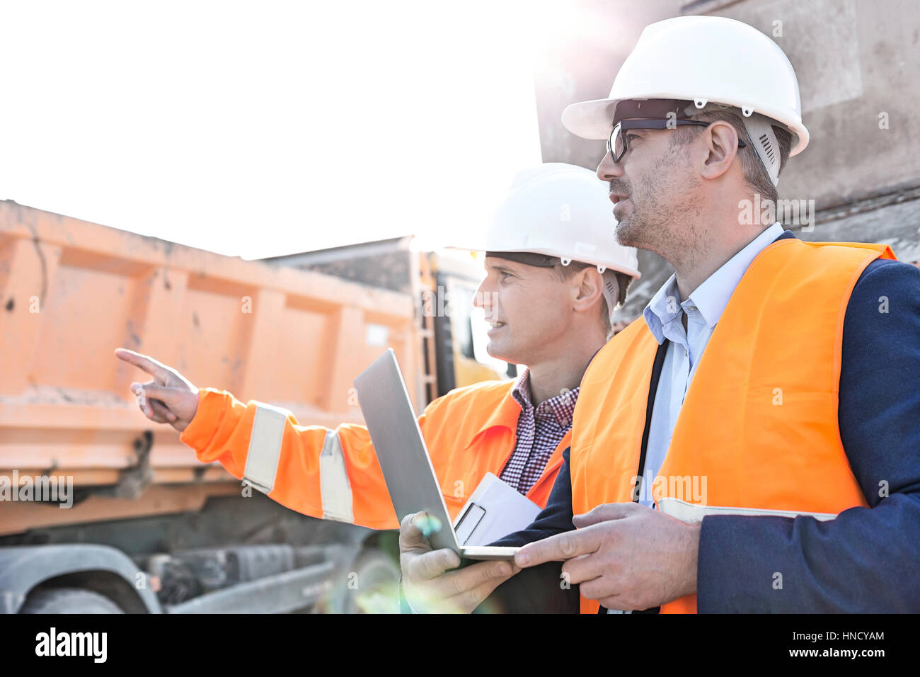 Supervisor showing something to colleague holding laptop at construction site Stock Photo
