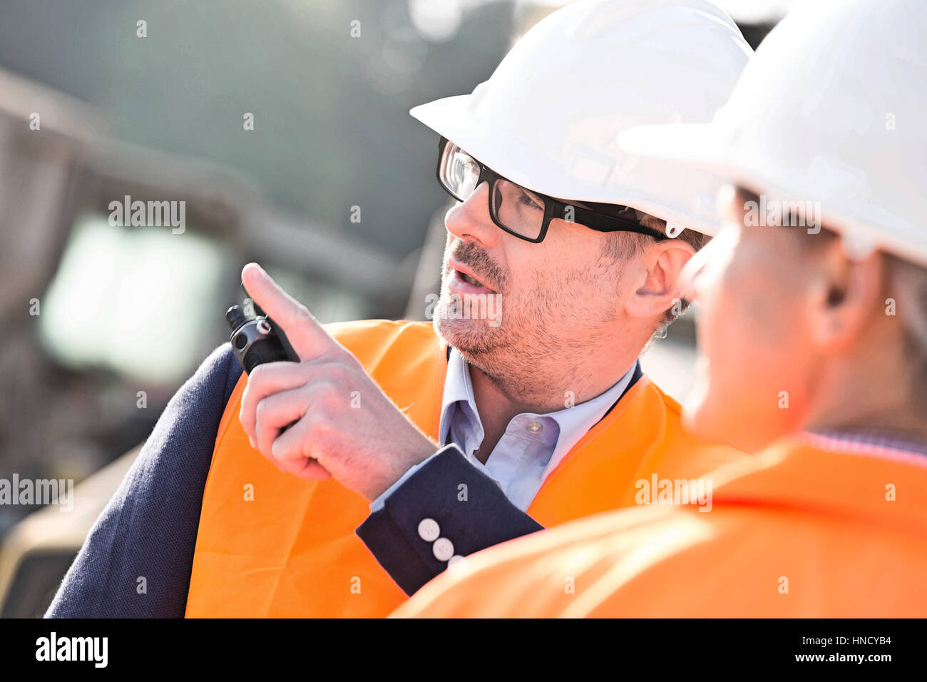 Supervisor showing something to colleague at construction site Stock Photo