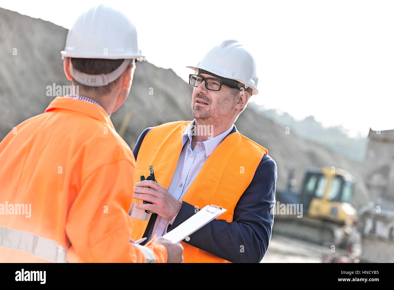 Architects discussing at construction site on sunny day - Stock Image