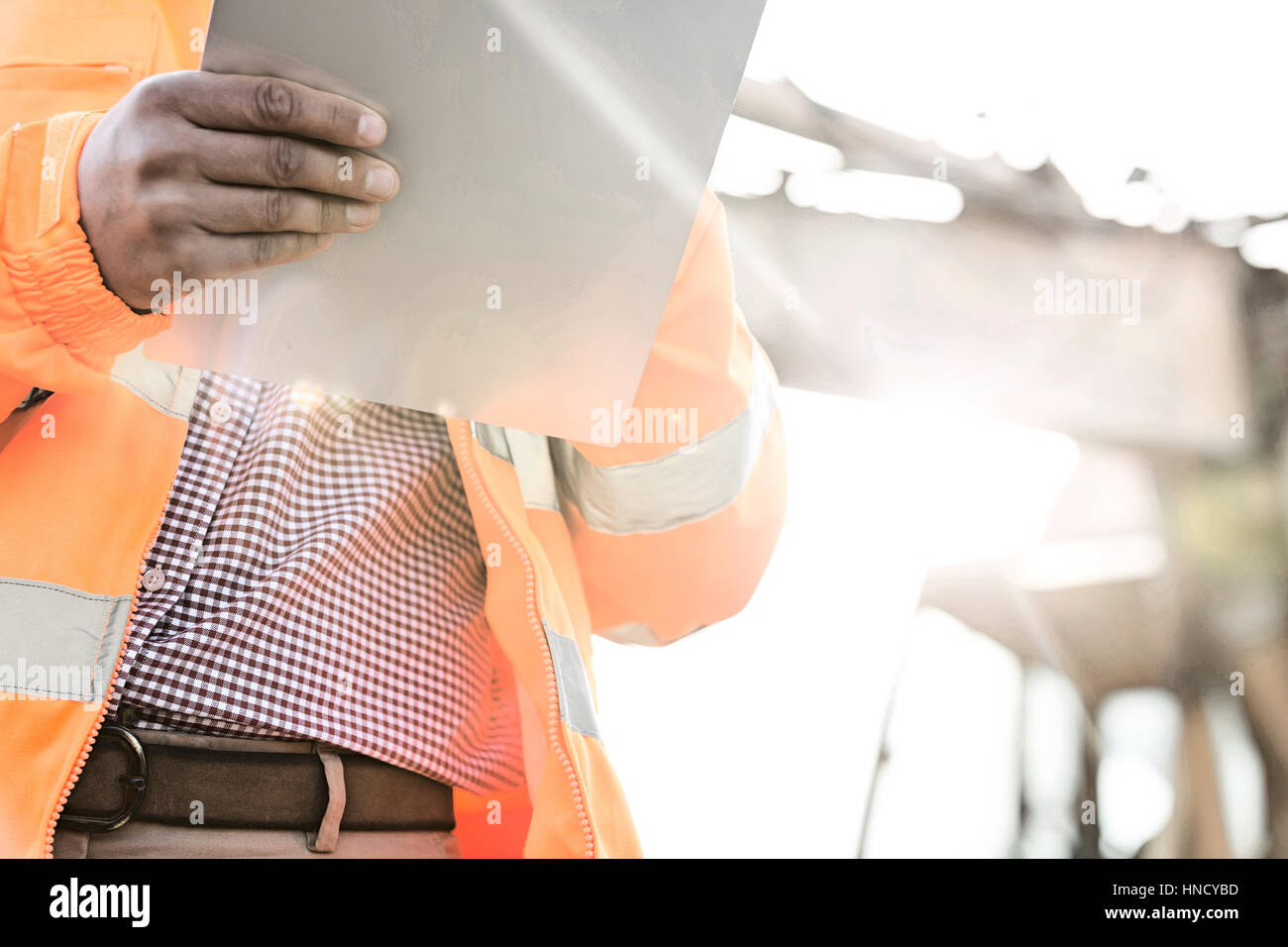 Midsection supervisor holding clipboard at construction site on sunny day - Stock Image
