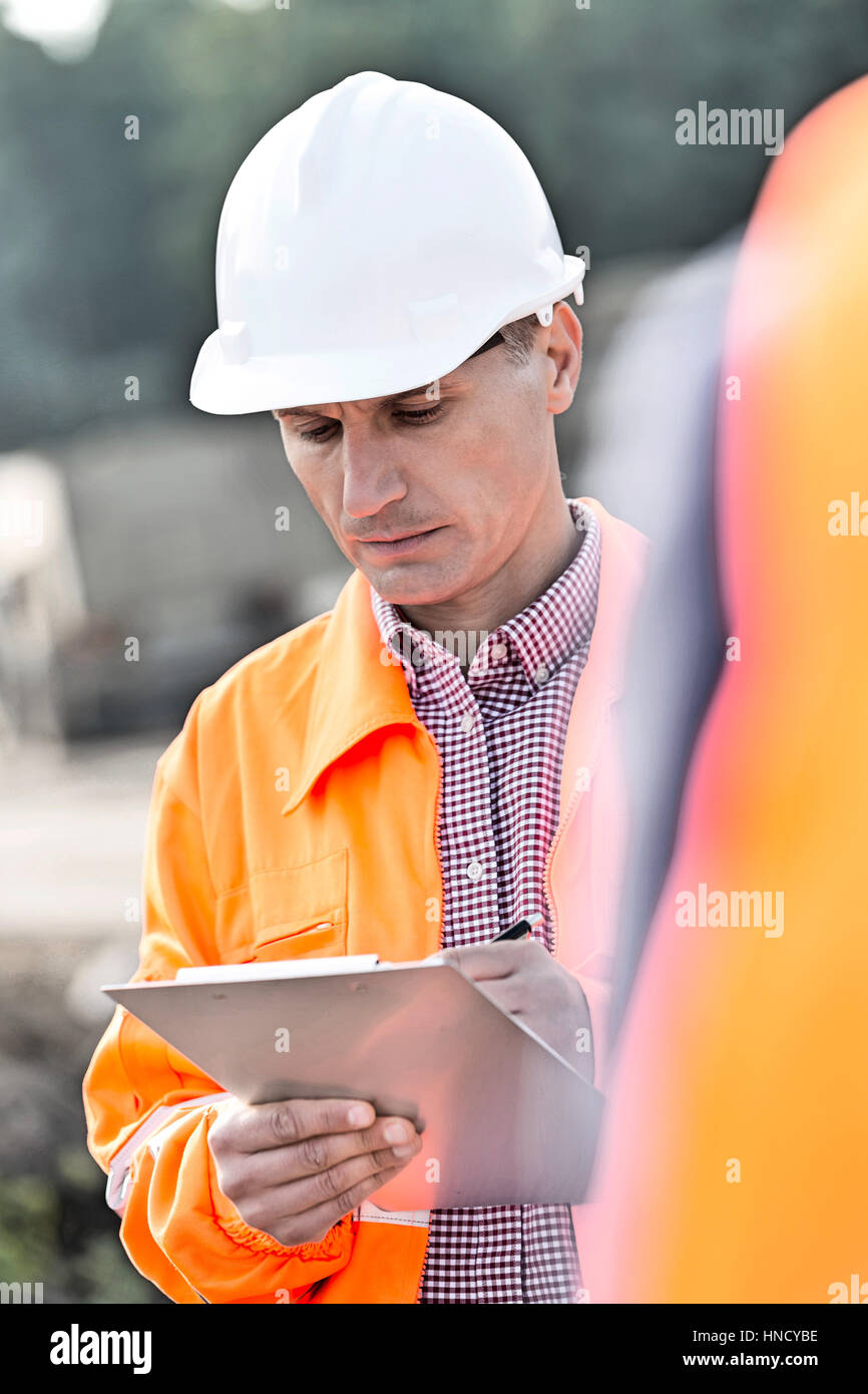 Supervisor writing on clipboard at construction site - Stock Image