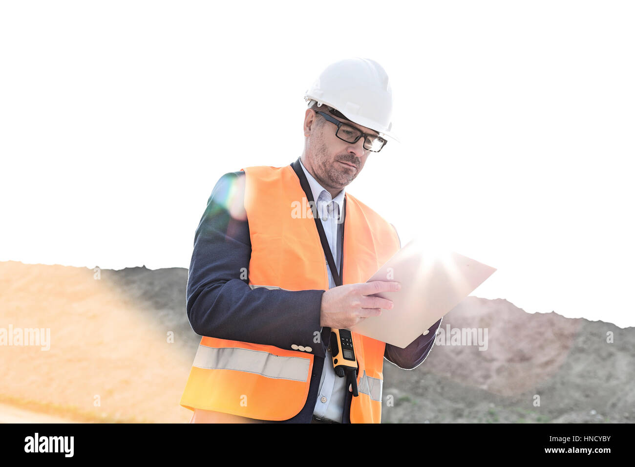 Male supervisor reading clipboard at construction site on sunny day - Stock Image