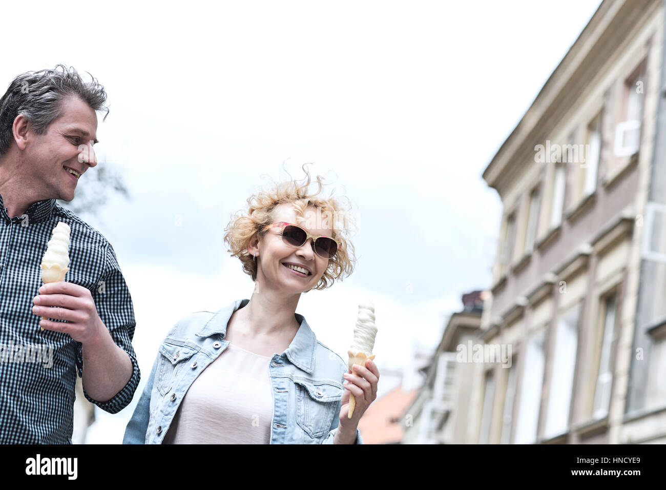 Smiling middle-aged couple holding ice cream cones on sunny day - Stock Image