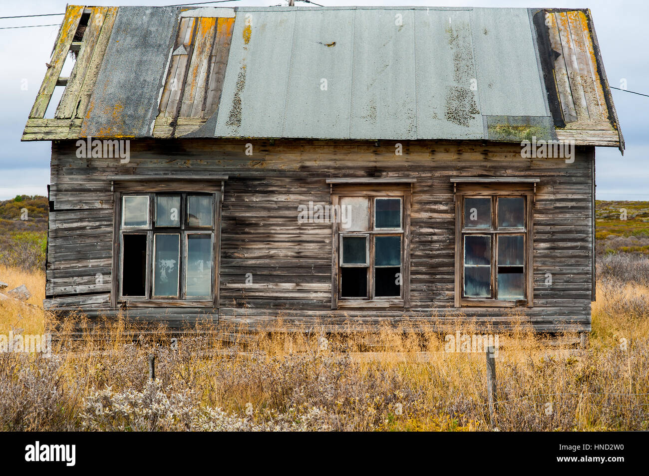 Old wooden decrepit shabby house in need of repair with damaged roof and broken windows - Stock Image