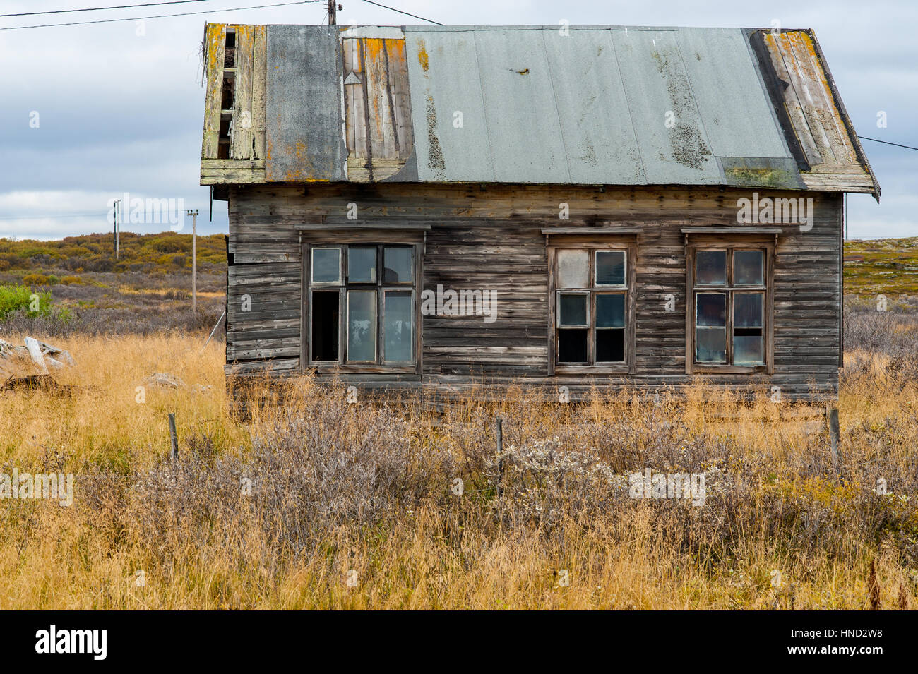 Old wooden decrepit house in need of repair with damaged roof and broken windows - Stock Image