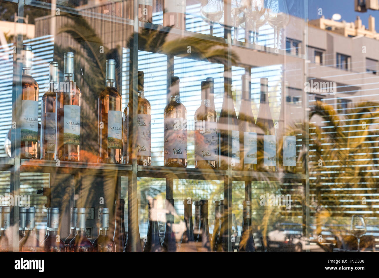 Porto architecture reflectiones in a window pane, colorful wine bottles blurred by the glass and sun rays play. - Stock Image