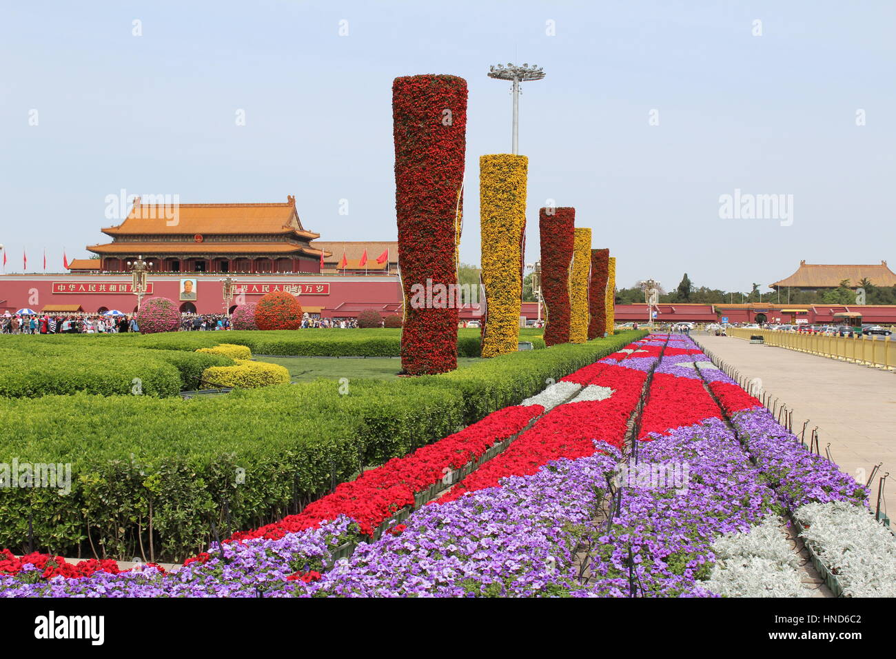 Flowers and patterns at Tiananmen square in front of The Forbidden City with picture og Chairman Mao - Stock Image