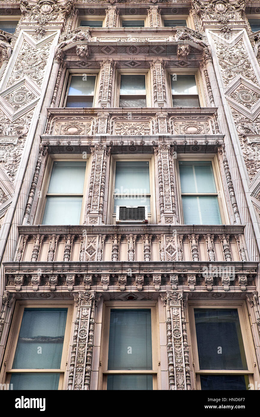 Sections of a terra cotta facade in french renaissance style with elaborate decorations around the windows of a - Stock Image