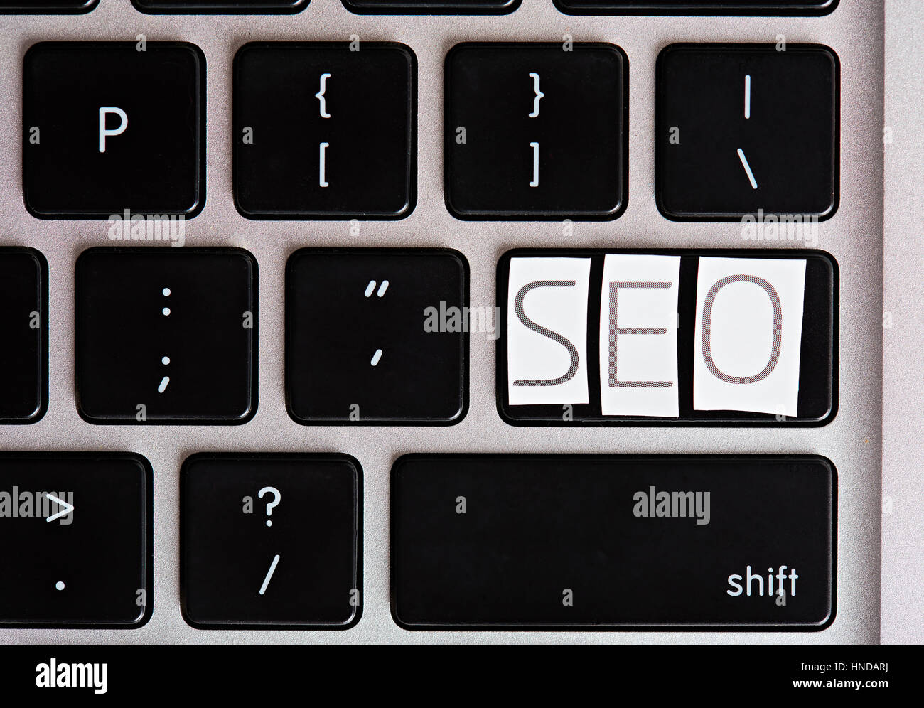 SEO letters on keyboard button cutout from magazine Stock