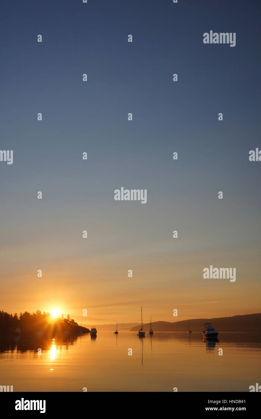 Sunrise over boaters at anchor in Lopez Sound just off Spencer Spit, Spencer Spit State Park, Washington, USA - Stock Image